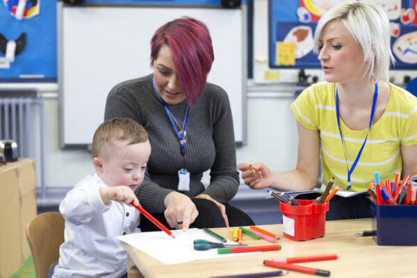 Nursery teacher sitting with a parent and her Down Syndrome son in the classroom. they are discussing the little boys progress.